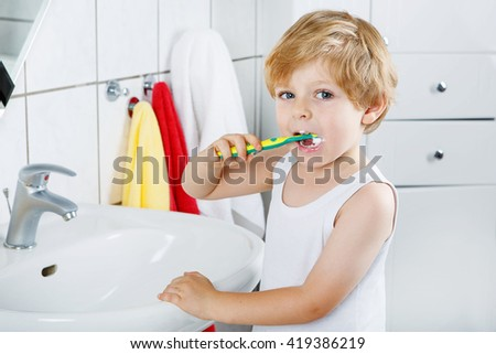 Little blond boy learning brushing his teeth in domestic bath. Kid learning how to stay healthy. Health care concept.
