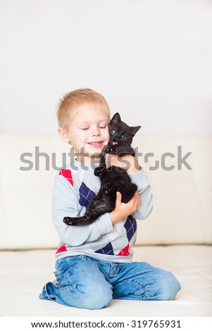 little blond boy playing with a black kitten on a white leather couch smiling