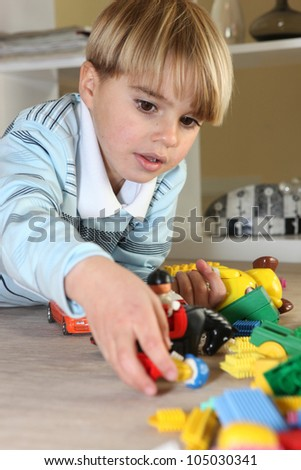 Little blond boy playing with toys - stock photo
