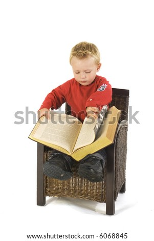 Little blond boy with heavy book to read