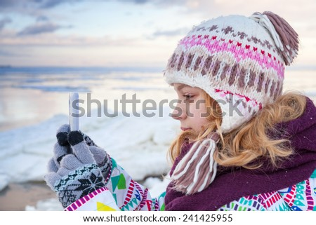 Little blond Caucasian girl taking pictures on her smartphone photo camera - stock photo