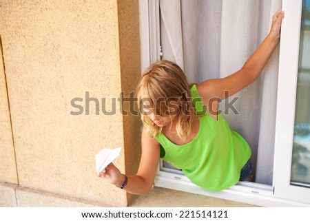 Little blond Caucasian girl with paper plane in the window - stock photo