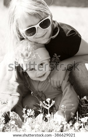Little blond Caucasian sisters hugging in a sunny Summer day. Closeup sepia toned monochrome portrait - stock photo