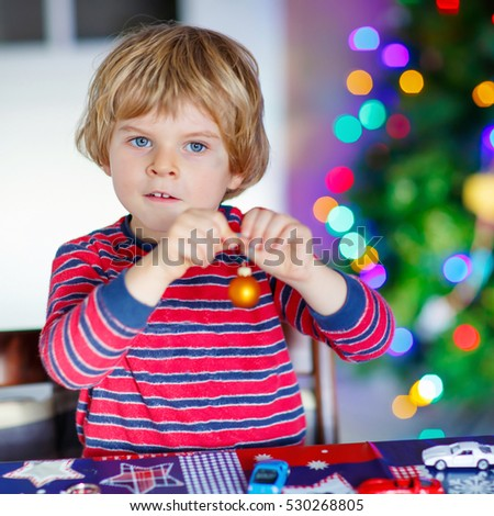 Little blond child playing with cars and toys at home, indoor. Cute happy funny kid boy having fun with gifts. Colorful lights on background. Christmas time concept.