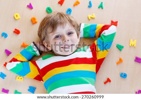 Little blond child playing with lots of colorful plastic letters, indoor. Kid boy wearing colorful shirt and having fun with learning reading - stock photo