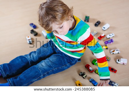 Little blond child playing with lots of toy cars indoor. Kid boy wearing colorful shirt and having fun. - stock photo