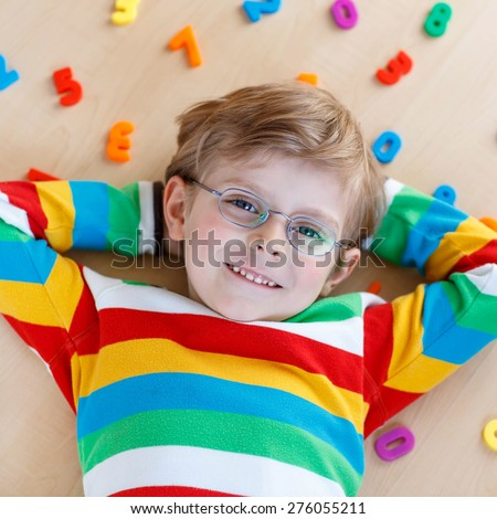 Little blond child with glasses playing with lots of colorful plastic digits or numbers, indoor. Kid boy wearing colorful shirt and having fun with learning math - stock photo