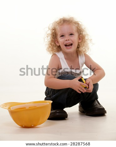 Little blond curly hair three year old boy wearing white muscle top and jeans and yellow hard hat sitting on floor with tape measure and grown up mans shoes - stock photo