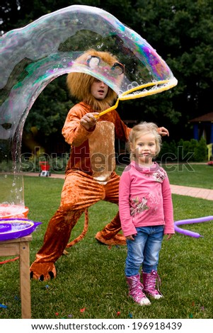 little blond girl and lion playing with soap bubble at the kids birthday party - stock photo