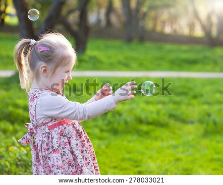Little blond girl catching soap bubbles. Selective focus and space for text - stock photo