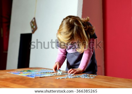 little blond girl doing a jigsaw puzzle - stock photo