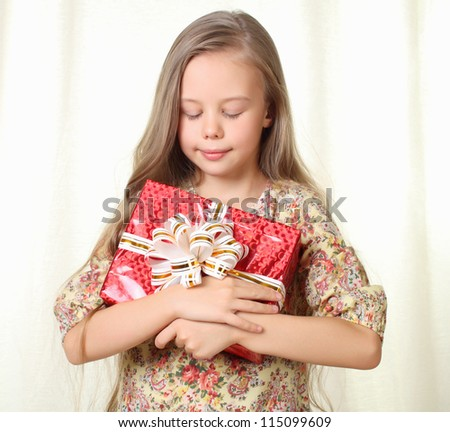 Little blond girl holding a red glamorous gift with pleasure - stock photo