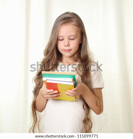 Little blond girl holding different books and looking on it - stock photo
