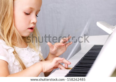little blond girl in beautiful white dress playing on white piano, closeup  - stock photo