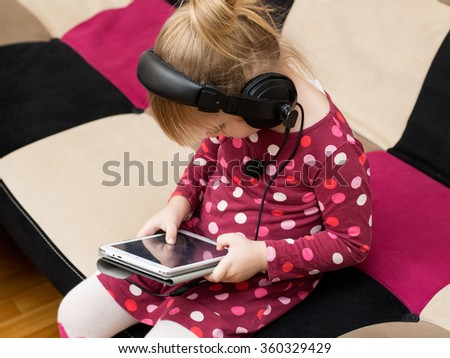 Little blond girl in the headphones with the tablet is playing. Serious face - stock photo
