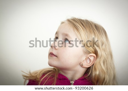 Little blond girl looking up - stock photo