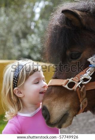 little blond girl loves her pony funny portrait - stock photo