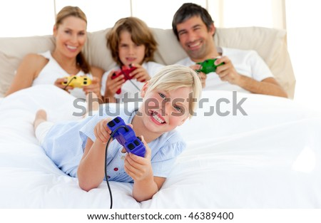 Little blond girl playing video game with her family in the bedroom - stock photo