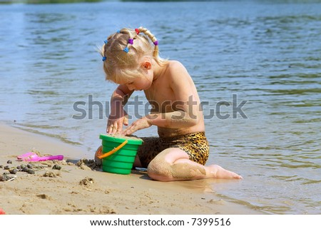 Little blond girl plays on beach with toy bucket in hot summer day. Shot in Ukraine.
