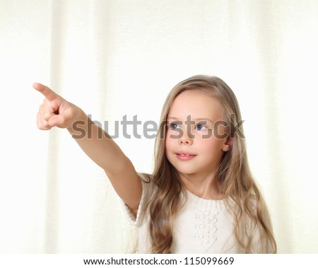 Little blond girl points direction by forefinger - stock photo