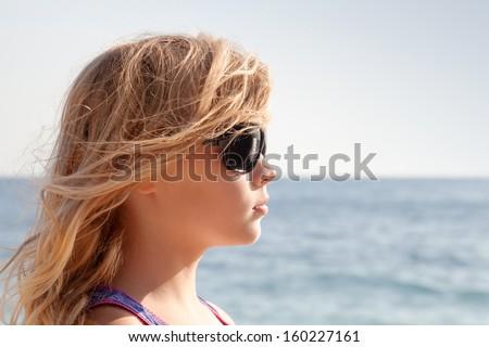 Little blond girl profile portrait with sunglasses on the summer sea coast - stock photo