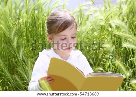little blond girl reading book between green spikes meadow garden