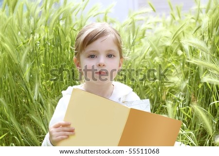 little blond girl reading book between green spikes meadow garden - stock photo