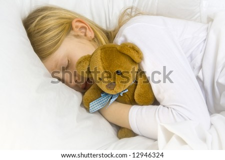 Little blond girl wearing white blouse in white bedchlothes - stock photo