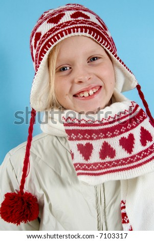 Little blond girl wearing woolen cap, scarf and gloves