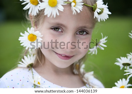 little blond girl with a crown of daisies in her hair - stock photo