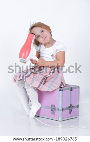 Little blond girl with a hairdryer sitting on a makeup beauty case in a pink and white dress isolated on white in studio - stock photo