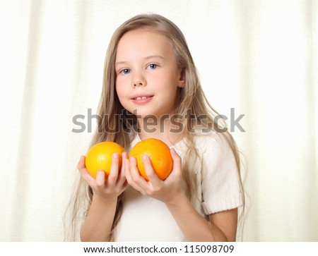 Little blond girl with oranges smiling and looking to camera - stock photo