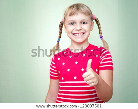 Little blond girl with pigtails smiles and show thumb up