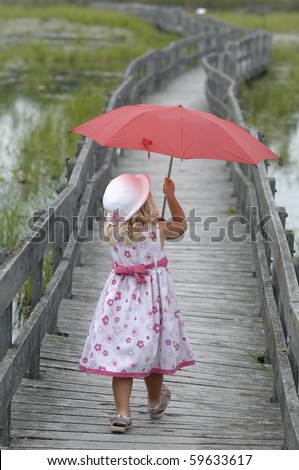 Little blond girl with the red umbrella walks on the boardwalk.
