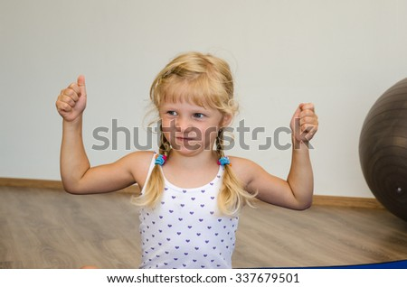 little blond girl with winner gesture in gym