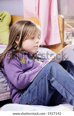 little blond girl writing over a bed - stock photo