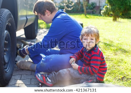 Little blond kid boy and his father changing wheels on car with pneumatic wrench. Man in uniform teaching his son working with tools. - stock photo