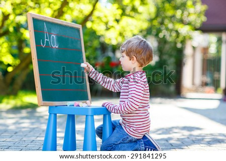 Little blond kid boy at blackboard practicing writing letters and mathematics, outdoor school or nursery. Kid learning and schoolboy concept. On summer sunny day. Back to school. - stock photo