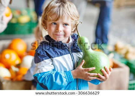 Little blond kid boy holding green pumpkin on halloween or thanksgiving harvest festival or patch, outdoors