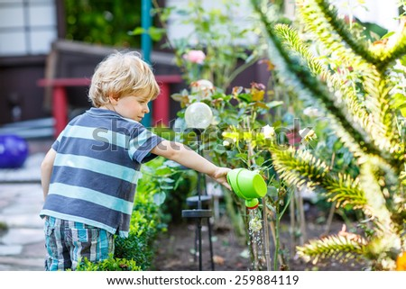 Little blond kid boy playing with water can toy in summer garden. On warm summer day, happy leisure with children outdoors. - stock photo
