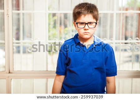 Little blond kid with glasses looking all angry and pissed off at home - stock photo