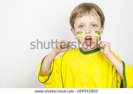 Little blond preschool boy of 7 years with football watching TV