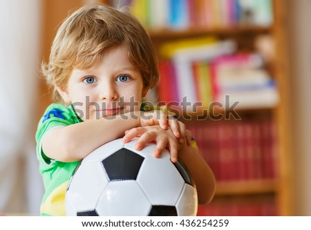 Little blond preschool kid boy of 4 years with football watching soccer cup game on tv. Adorable child enjoying game, fan of his favorite team - stock photo