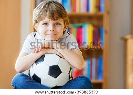 Little blond preschool kid boy with ball watching soccer european cup game on tv. Funny child fan having fun and cheering winning football team. Champions league concept. - stock photo