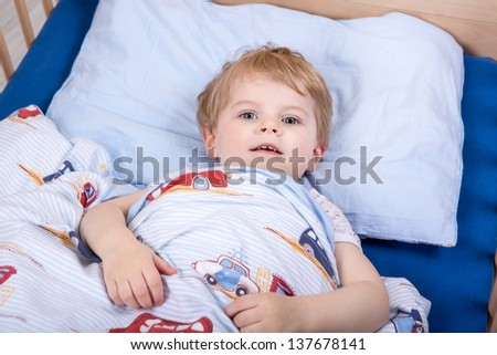 Little blond toddler boy in bed before sleeping - stock photo