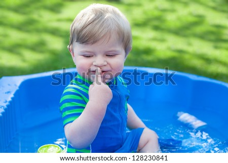 Little blond toddler boy playing with water in summer garden on sunny day - stock photo