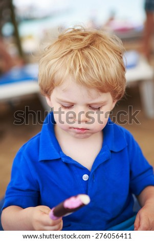 Little blond toddler eating chocolate and strawberry ice cream pop, outdoors