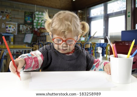 little blond toddler girl making a drawing in a classroom - stock photo