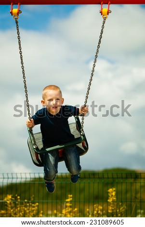 Little blonde boy having fun at the playground. Child kid playing on a swing outdoor. Happy active childhood. - stock photo