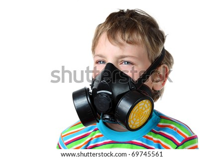 Little blonde boy screws up ones eyes and look toward in black respirator on a white background - stock photo